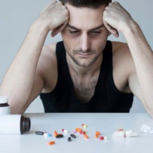 Despairing man in front of pills needs to detox from percocet